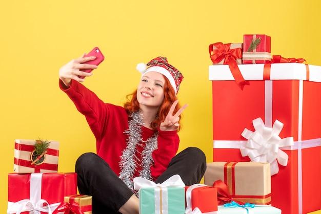 Vooraanzicht van de jonge vrouw die rond kerstmis zit presenteert selfie op gele muur