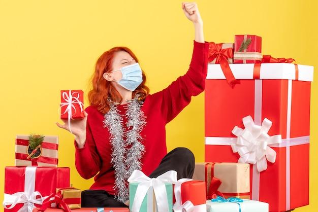 Vooraanzicht van de jonge vrouw die rond kerstmis zit stelt in masker op gele muur voor