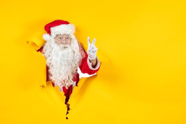 Vooraanzicht van de kerstman die door gescheurde document gele muur kijkt