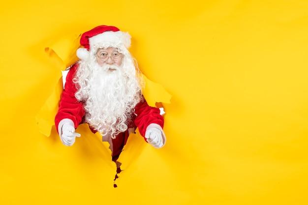 Vooraanzicht van de kerstman die door gescheurde gele muur kijkt