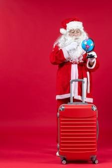 Vooraanzicht van de kerstman die met zak kleine bol houdt en voor reis op rode muur voorbereidingen treft