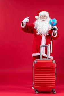 Vooraanzicht van de kerstman met de bol van de zakholding en het voorbereiden van reis op rode muur