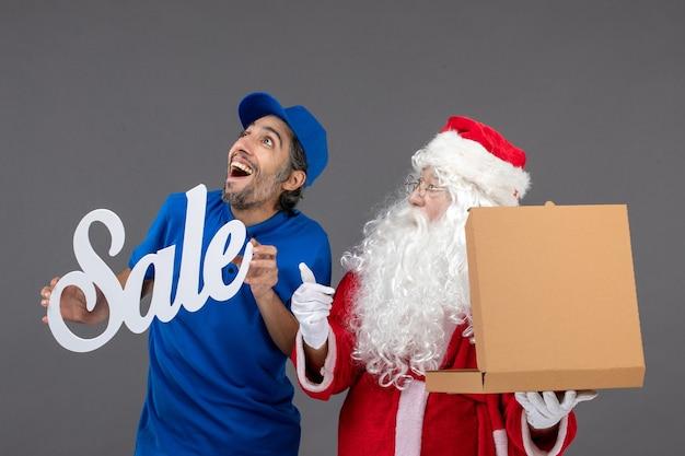 Vooraanzicht van de kerstman met de mannelijke verkoopbanner van de koeriersholding en het openen van voedseldoos op de grijze muur