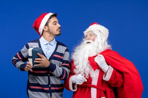 Vooraanzicht van de kerstman met een jonge man die het cadeau op de blauwe muur opent