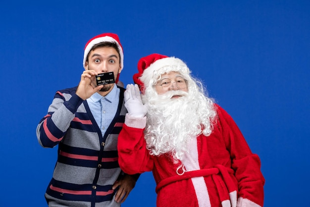 Vooraanzicht van de kerstman met een jonge man met een bankkaart op de blauwe muur