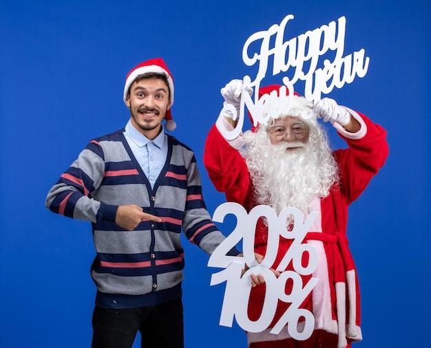 Vooraanzicht van de kerstman met een jonge man met happy new year en cijfers op de blauwe muur