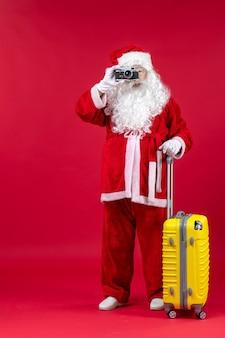 Vooraanzicht van de kerstman met gele zak die foto met camera op de rode muur neemt