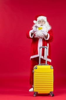 Vooraanzicht van de kerstman met gele zak met gele bankkaart op de rode muur