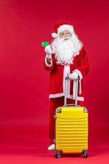 Vooraanzicht van de kerstman met gele zak met groene bankkaart op de rode muur
