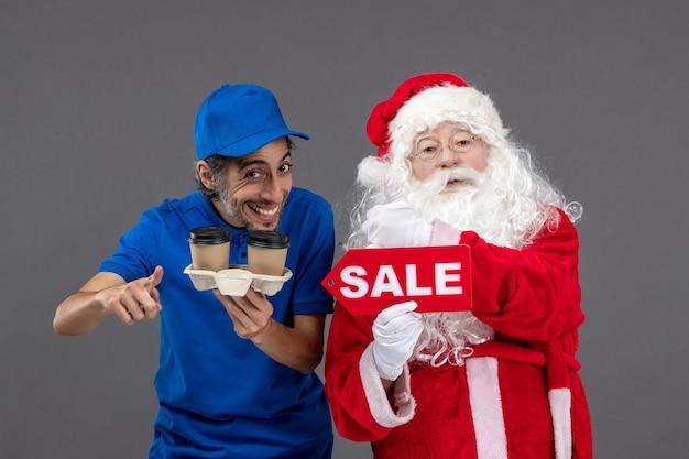 Vooraanzicht van de kerstman met het mannelijke verkoop schrijven van de koeriersholding en koffie op de grijze muur