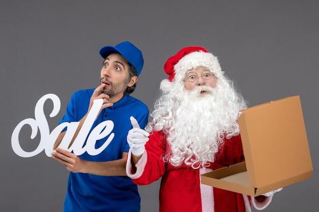 Vooraanzicht van de kerstman met het mannelijke verkoop schrijven van de koeriersholding en lege voedseldoos op de grijze muur