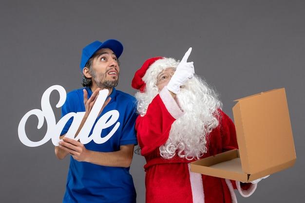 Vooraanzicht van de kerstman met het mannelijke verkoop schrijven van de koeriersholding en voedseldoos op grijze muur