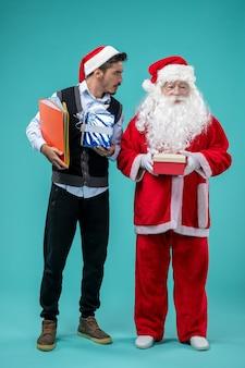 Vooraanzicht van de kerstman met jong mannetje en cadeautjes op blauwe muur