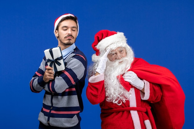 Vooraanzicht van de kerstman met jonge man die aanwezig is op de blauwe muur