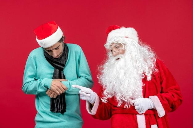Vooraanzicht van de kerstman met jonge man die op de rode muur staat