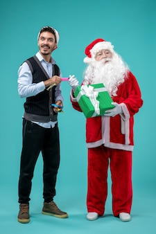 Vooraanzicht van de kerstman met jonge man en heden op blauwe muur