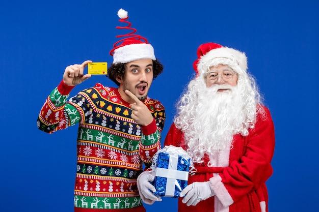 Vooraanzicht van de kerstman met jonge man met bankkaart en aanwezig op de blauwe muur
