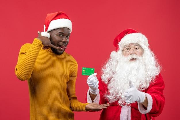 Vooraanzicht van de kerstman met jonge man met groene bankkaart op de rode muur