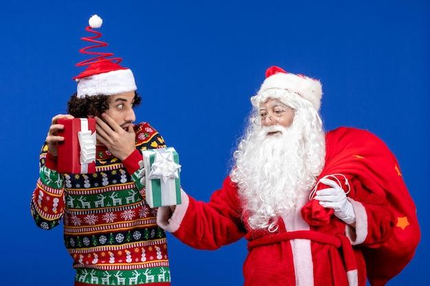 Vooraanzicht van de kerstman met jonge man met kerstcadeautjes op de blauwe muur