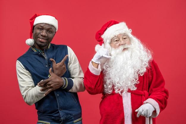 Vooraanzicht van de kerstman met jonge man op de rode muur