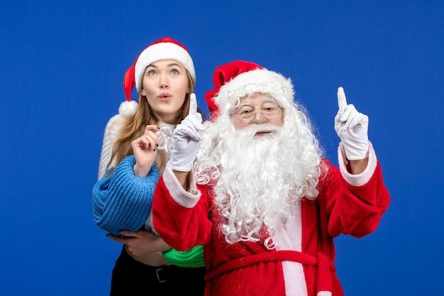 Vooraanzicht van de kerstman met jonge mooie vrouw op de blauwe muur