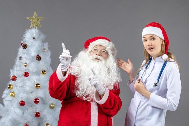 Vooraanzicht van de kerstman met jonge vrouw arts op de grijze muur