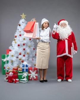 Vooraanzicht van de kerstman met jonge vrouw rond kerstboom en cadeautjes op de grijze muur