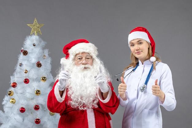 Vooraanzicht van de kerstman met jonge vrouwelijke arts op een grijze muur