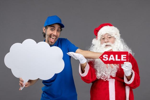 Vooraanzicht van de kerstman met mannelijk de wolkenteken van de koeriersholding en verkoopbanner op grijze muur