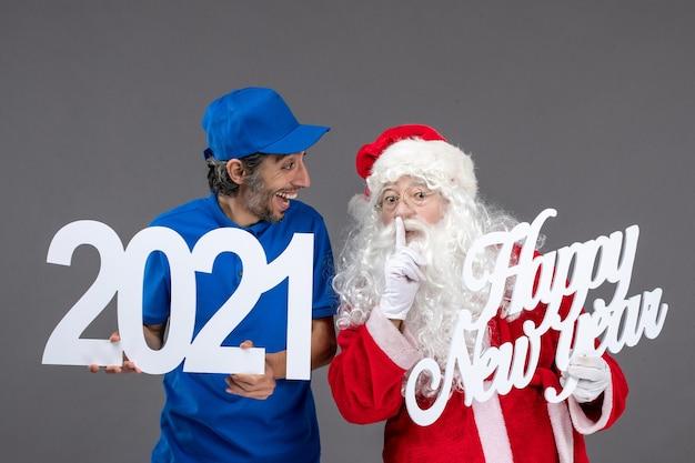 Vooraanzicht van de kerstman met mannelijke koerier die gelukkig nieuwjaar en 2021-planken op de grijze muur houdt