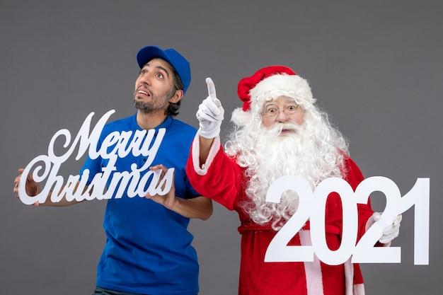 Vooraanzicht van de kerstman met mannelijke koerier die prettige kerstdagen en 2021-banner op een grijze muur houdt