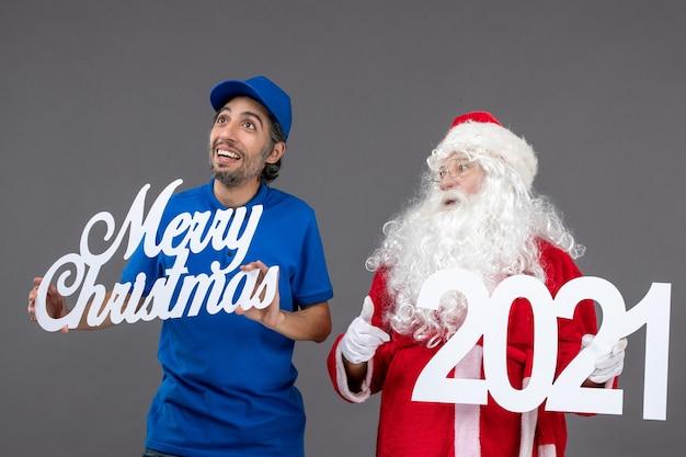 Vooraanzicht van de kerstman met mannelijke koerier die prettige kerstdagen en 2021-planken op de grijze muur houdt