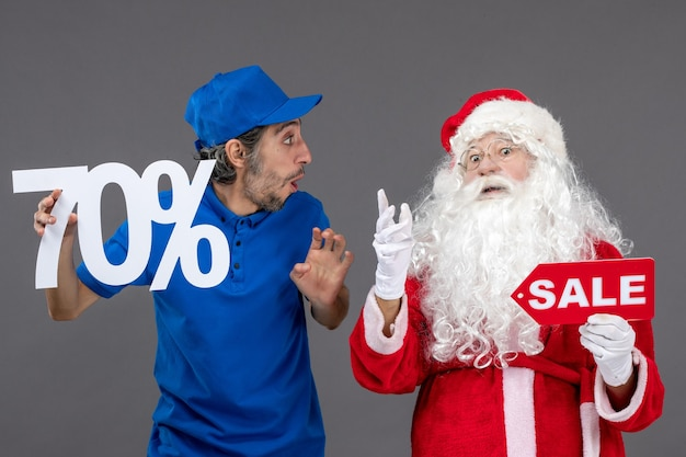 Vooraanzicht van de kerstman met mannelijke koerier die verkoopbanners op de grijze muur houdt