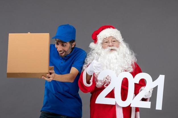 Vooraanzicht van de kerstman met mannelijke koerier die voedseldoos houdt en op de grijze muur schrijft