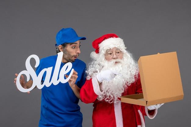 Vooraanzicht van de kerstman met mannelijke koeriersbedrijf verkoop banner en voedseldozen op de grijze muur