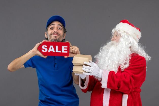 Vooraanzicht van de kerstman met mannelijke koeriersbedrijf verkoop banner en voedselpakketten op grijze muur