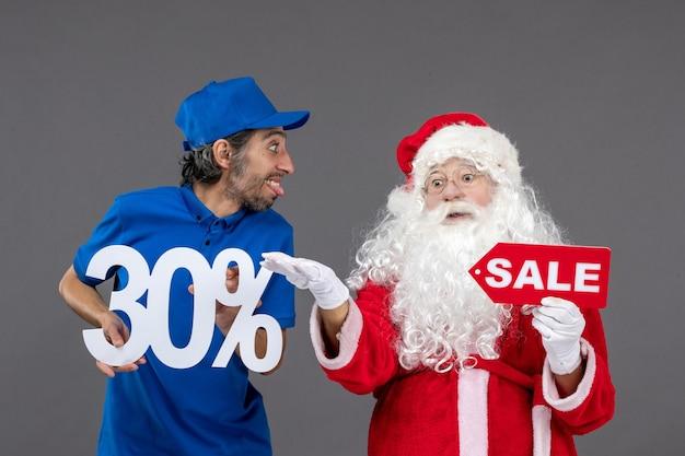 Vooraanzicht van de kerstman met mannelijke koeriersbedrijf verkoop banners op een grijze muur Gratis Foto