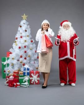 Vooraanzicht van de kerstman met vrouw rond kerstboom en cadeautjes op grijze muur
