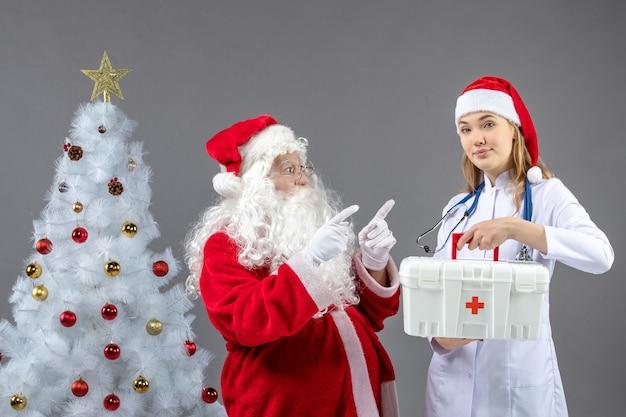 Vooraanzicht van de kerstman met vrouwelijke arts die ehbo-doos op de grijze muur houdt