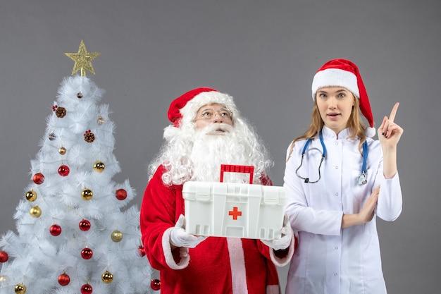 Vooraanzicht van de kerstman met vrouwelijke arts die hem een ehbo-doos op de grijze muur gaf