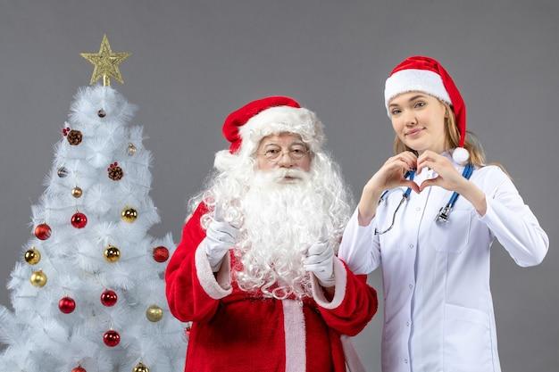 Vooraanzicht van de kerstman met vrouwelijke arts die liefde op grijze muur verzendt