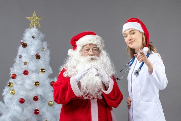 Vooraanzicht van de kerstman met vrouwelijke arts op de grijze muur