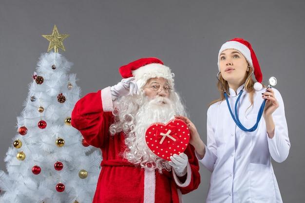 Vooraanzicht van de kerstman met vrouwelijke artsenholding op de grijze muur