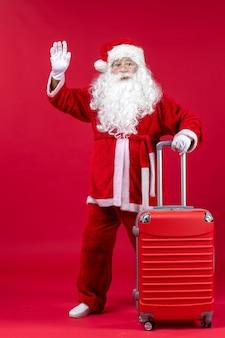Vooraanzicht van de kerstman met zijn rode tas op rode muur