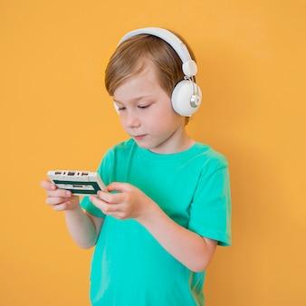 Vooraanzicht van de kleine jongen met muziek concept
