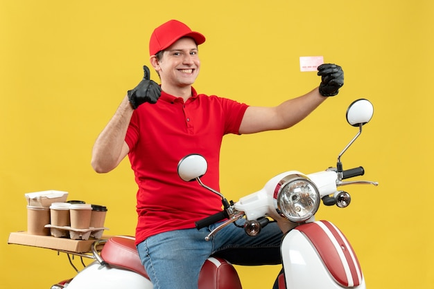 Vooraanzicht van de koeriersmens die rode blouse en hoedshandschoenen in medisch masker draagt die ordezitting op scooter bezorgen die bankkaart maakt die ok gebaar maken