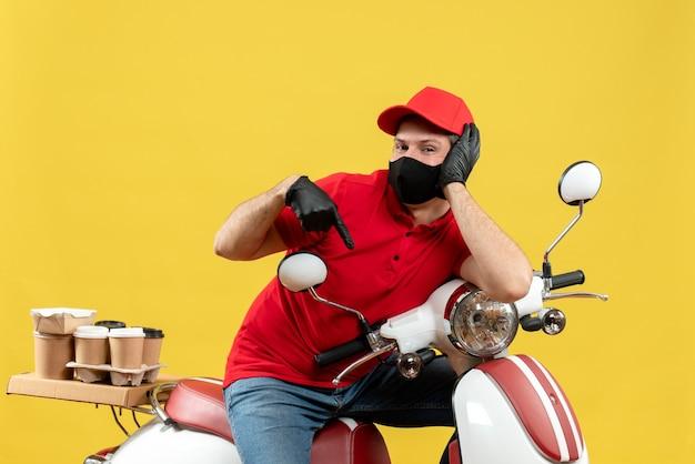 Vooraanzicht van de koeriersmens die rode blouse en hoedshandschoenen in medisch masker draagt die ordezitting op scooter naar beneden wijst