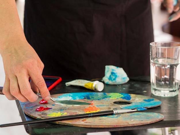 Vooraanzicht van de kunstenaar met behulp van verf palet