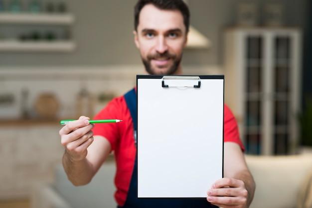 Vooraanzicht van de leveringsmens die blocnote tonen om voor orde te ondertekenen