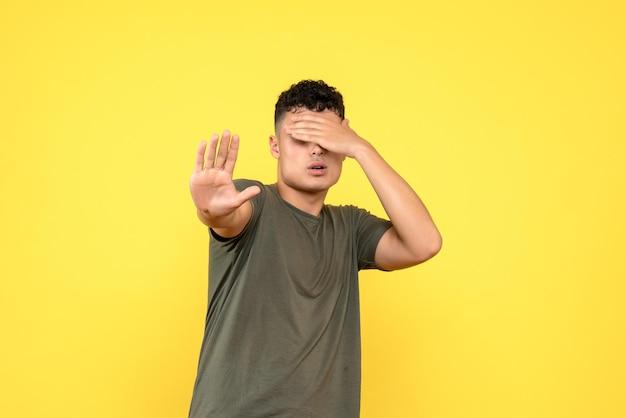 Vooraanzicht van de man bedekte zijn gezicht met zijn hand en stak zijn hand uit